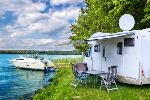 An RV with a satellite dish is parked next to a lake