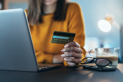 A white woman in a yellow sweater holds a credit card while looking at her laptop