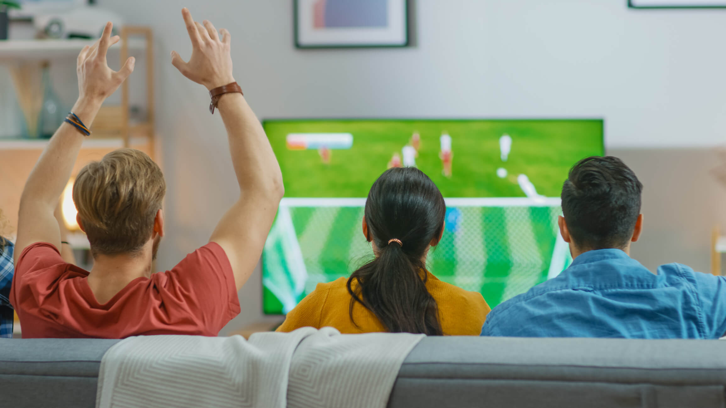 Three friends sitting on couch watching soccer game while one friend is cheering