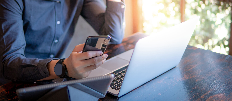 Man working on laptop using Cox internet holding smartphone