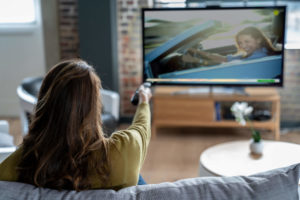 Woman watching TV on Playstation Vue
