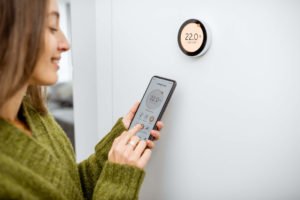 Woman stands in front of smart thermostat adjusting the temperature using her smartphone