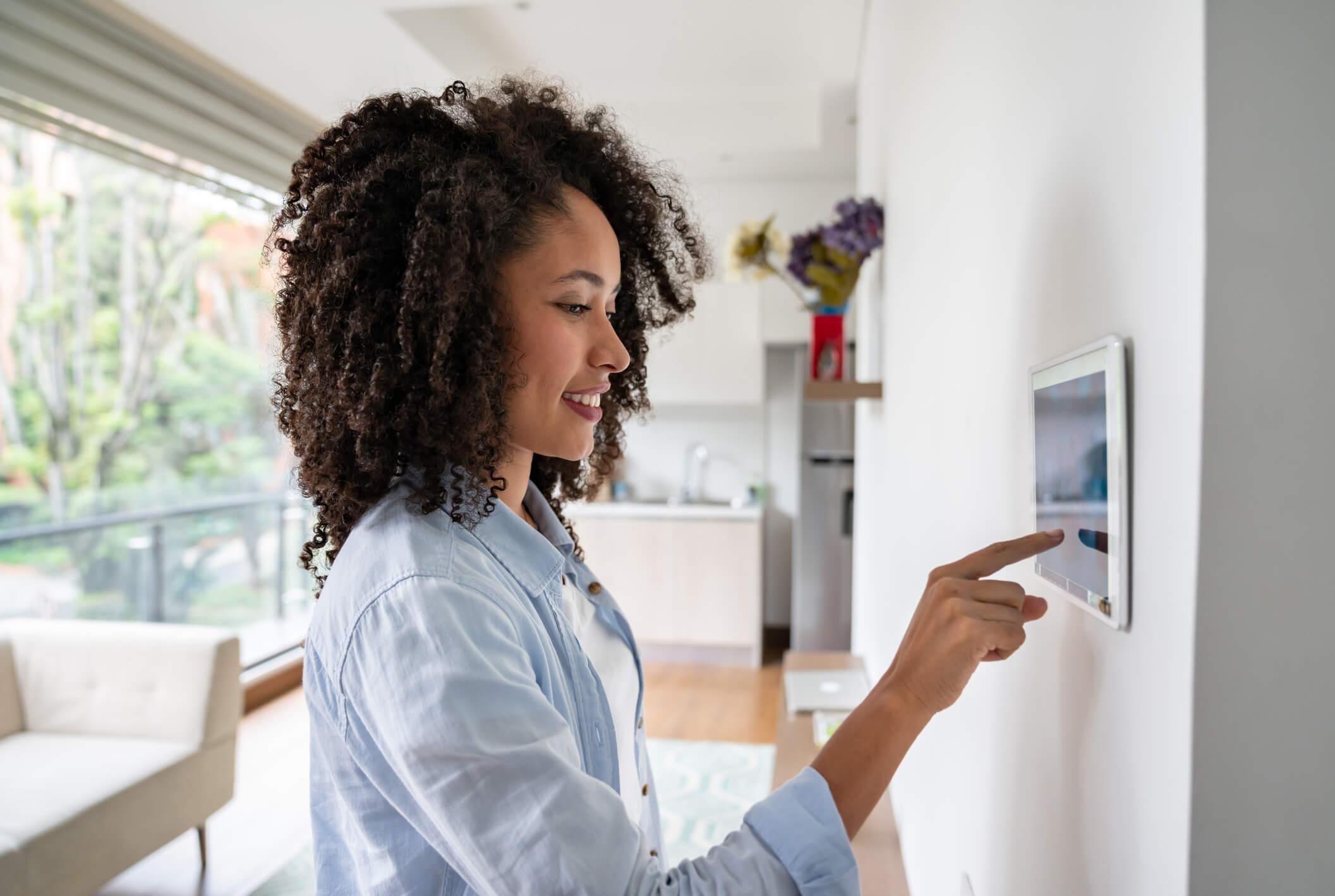 Woman adjusts smart home settings on a wall panel