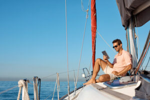 A white man in shorts and a T-shirt sits on the bow of his boat and uses a tablet