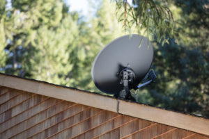 A satellite dish sits on top of a roof