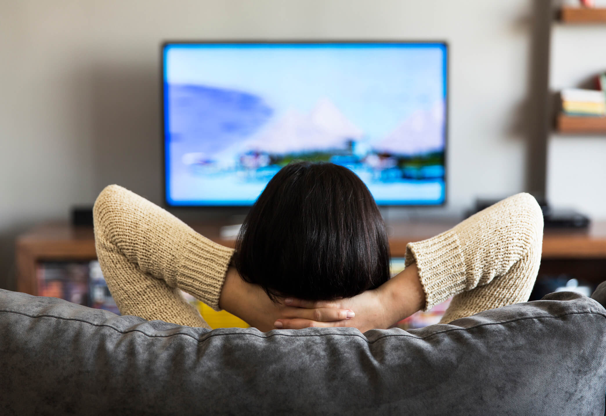 Woman laying back on couch watching verizon fios tv