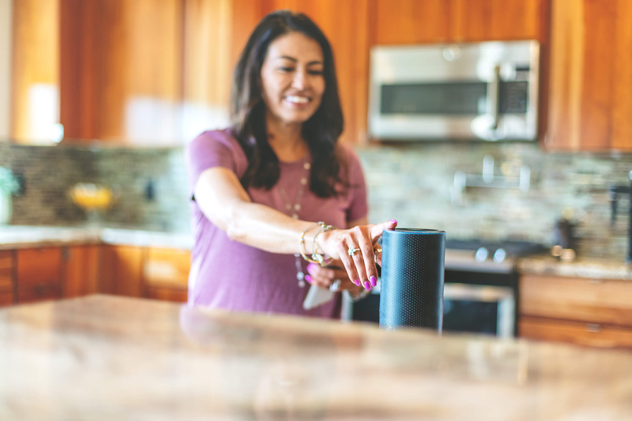 Woman in a kitchen tapping a smart speaker