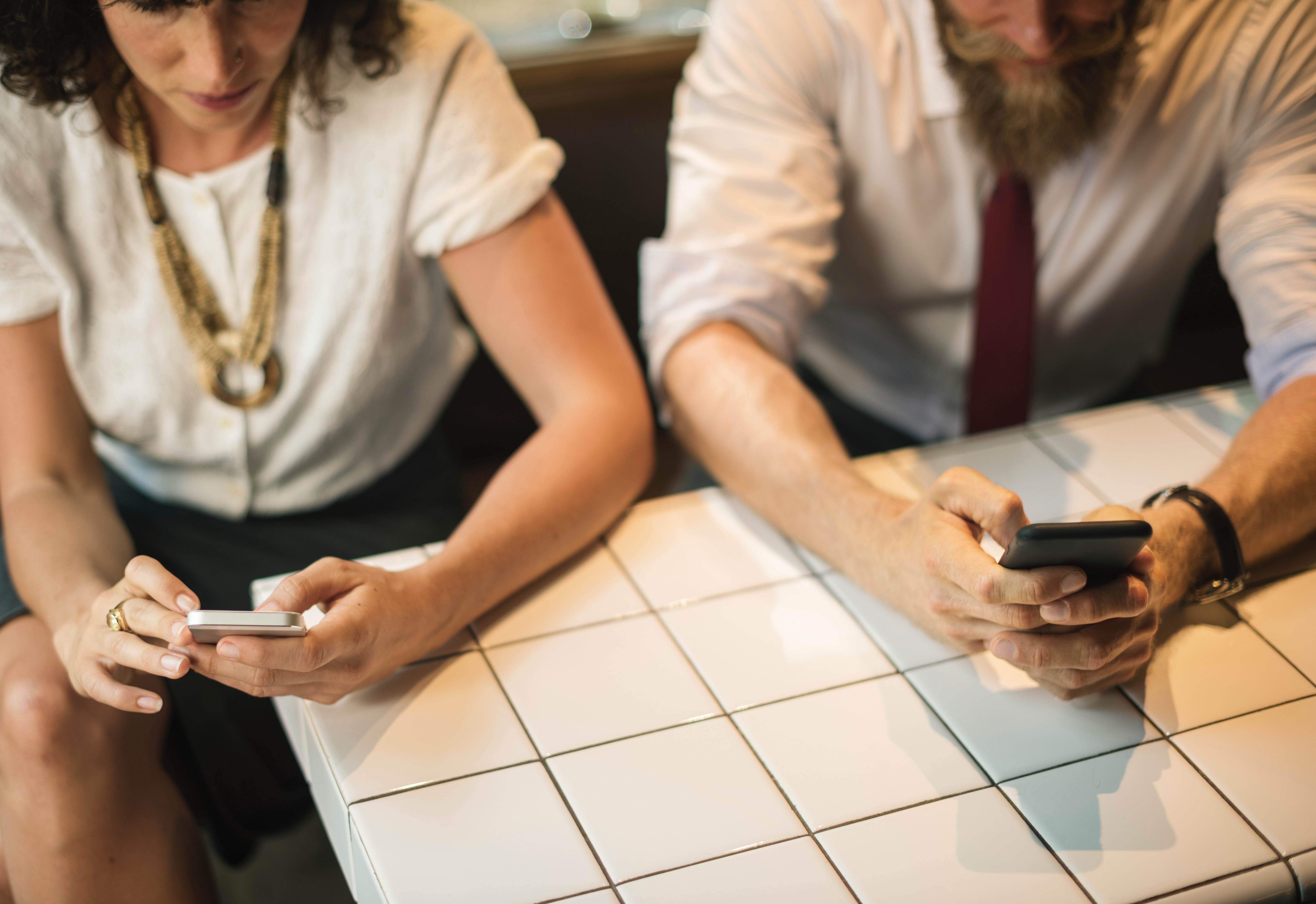 A man and a woman sitting next to each other at a table looking at their smartphones.