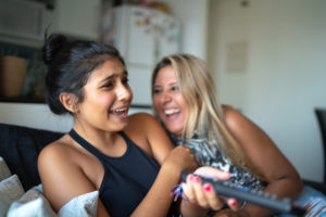 Mother and teen daughter laughing while watching tv on the sofa