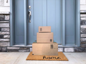 Brown cardboard packages piled on a porch in front of a blue front door