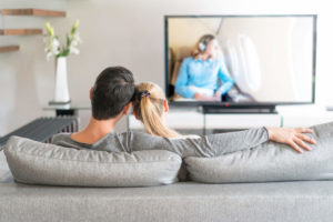 Couple sitting on couch in living room watching 4K TV