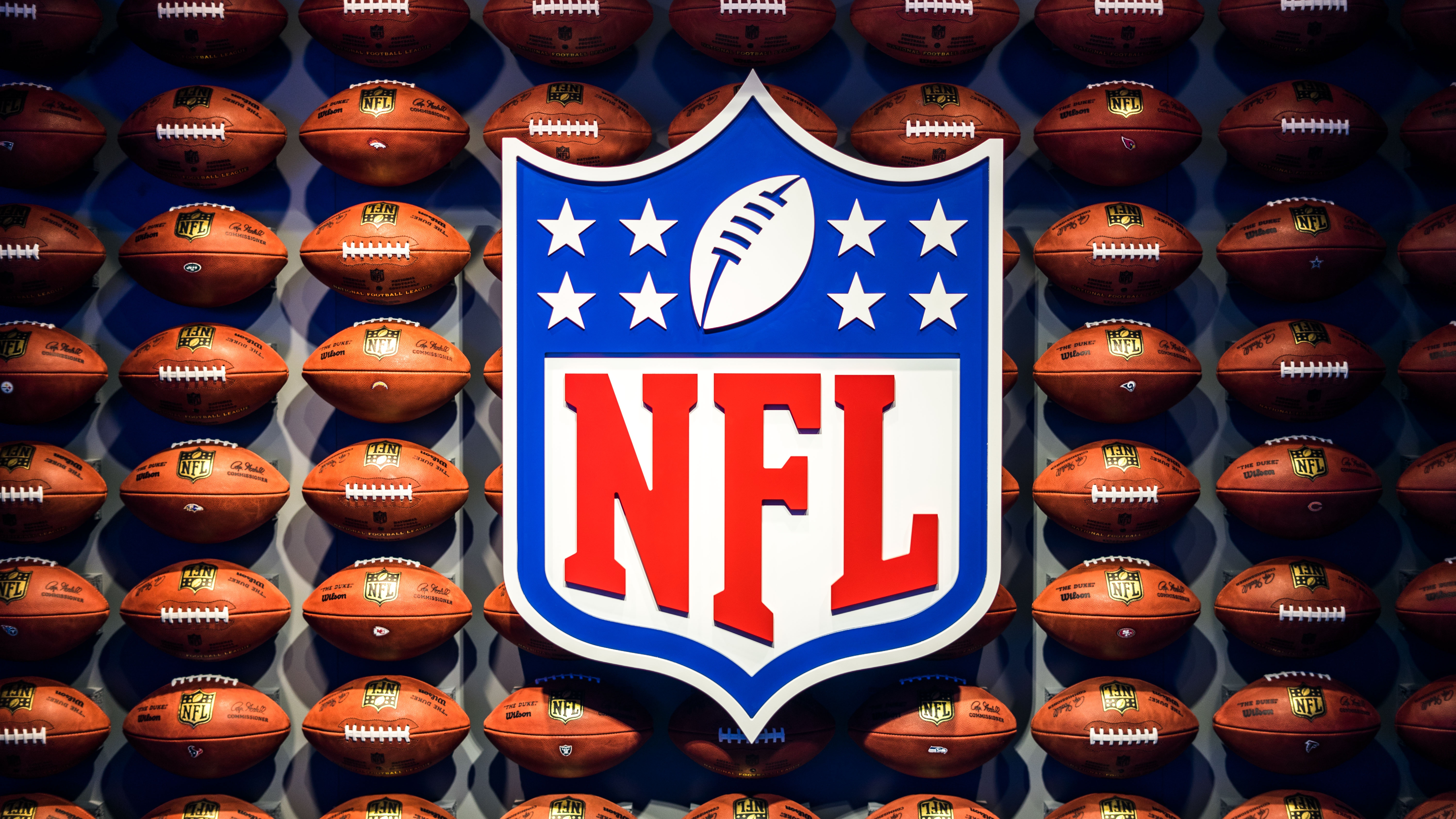 NFL logo in front of a wall of footballs