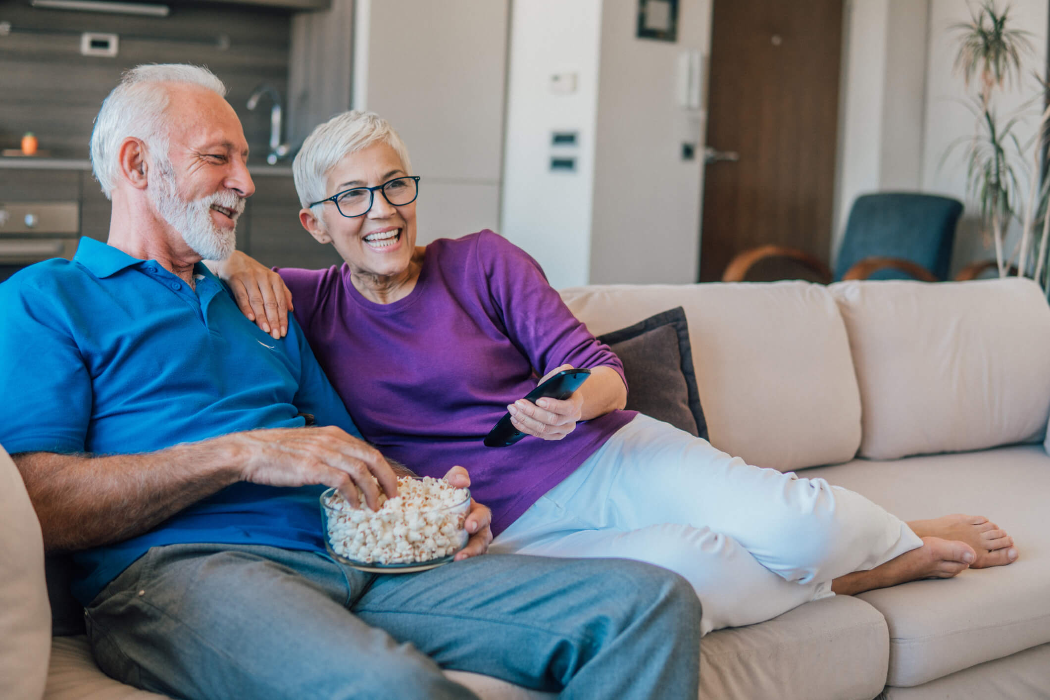 Older couple sitting on couch eating popcorn watching live TV streaming service