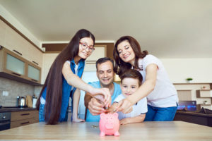 family of four putting money in a piggy bank