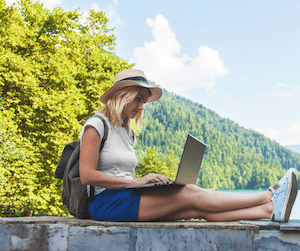 A woman uses a laptop while sitting outdoors