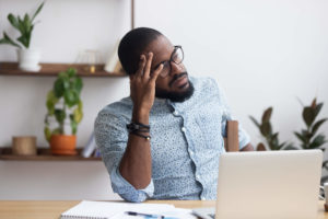 frustrated man sitting in front of a laptop