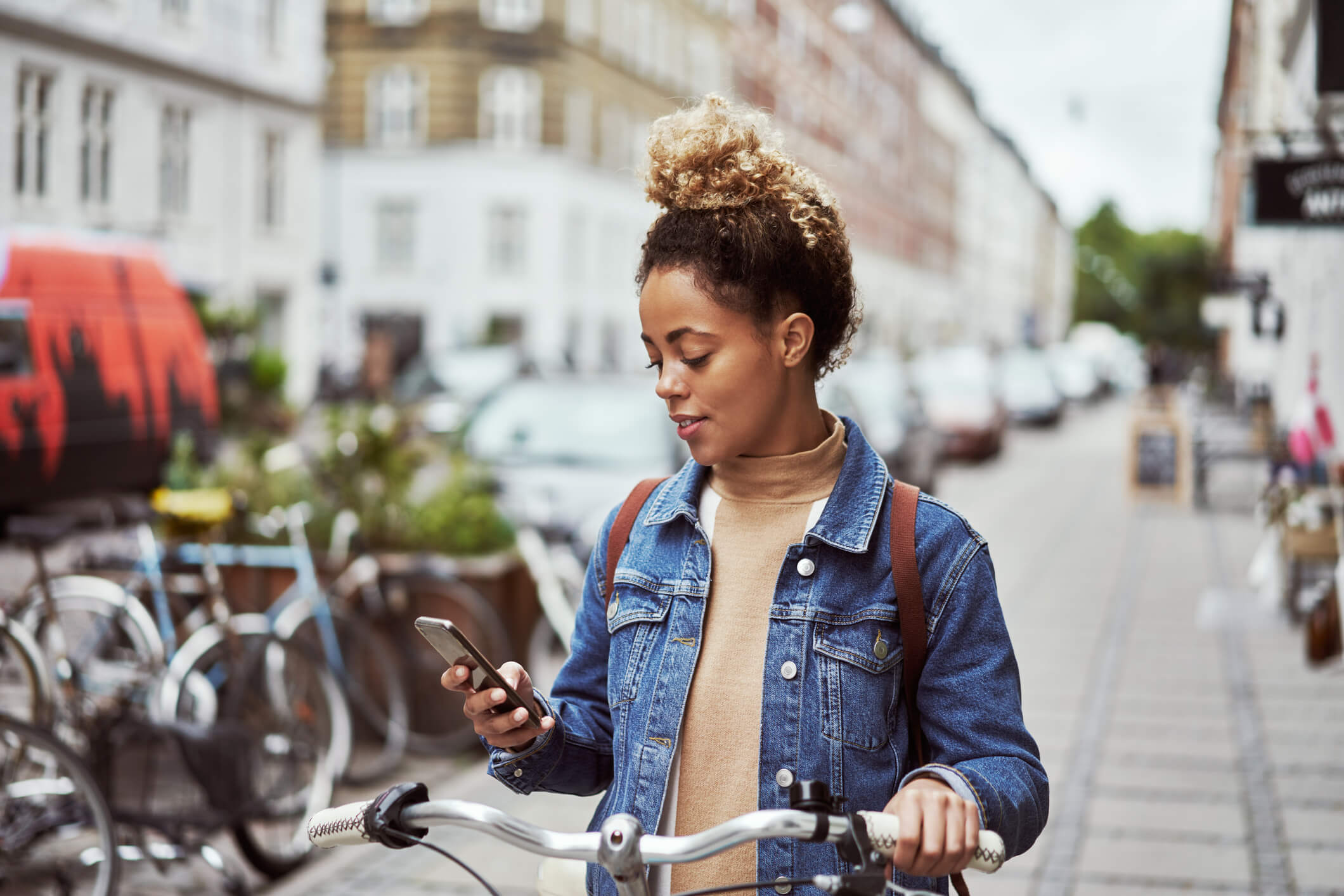 A woman with a bicycle is looking at her phone.