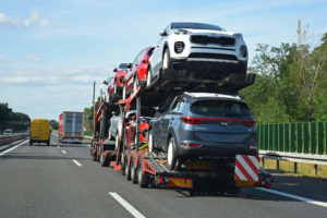 car shipping trailer driving down the highway