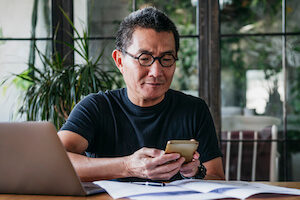 An older Asian man looks at his phone while working on his computer