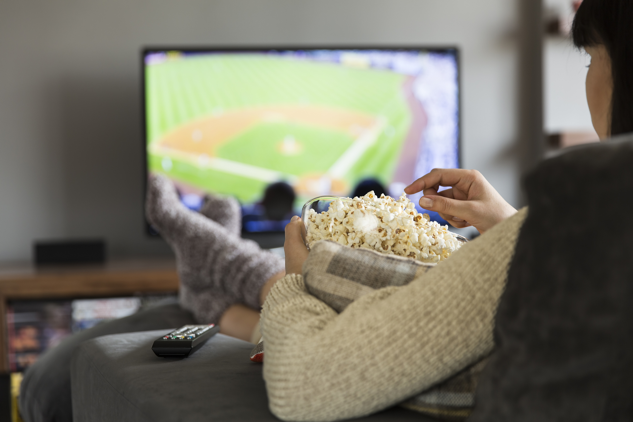 Woman watching baseball on couch while eating popcorn