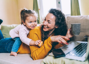 A white mother and daughter play on the couch while mom works on a laptop