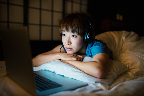 An Asian woman props her head up on a pillow while watching TV.