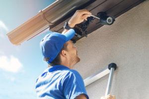 man installing a security camera