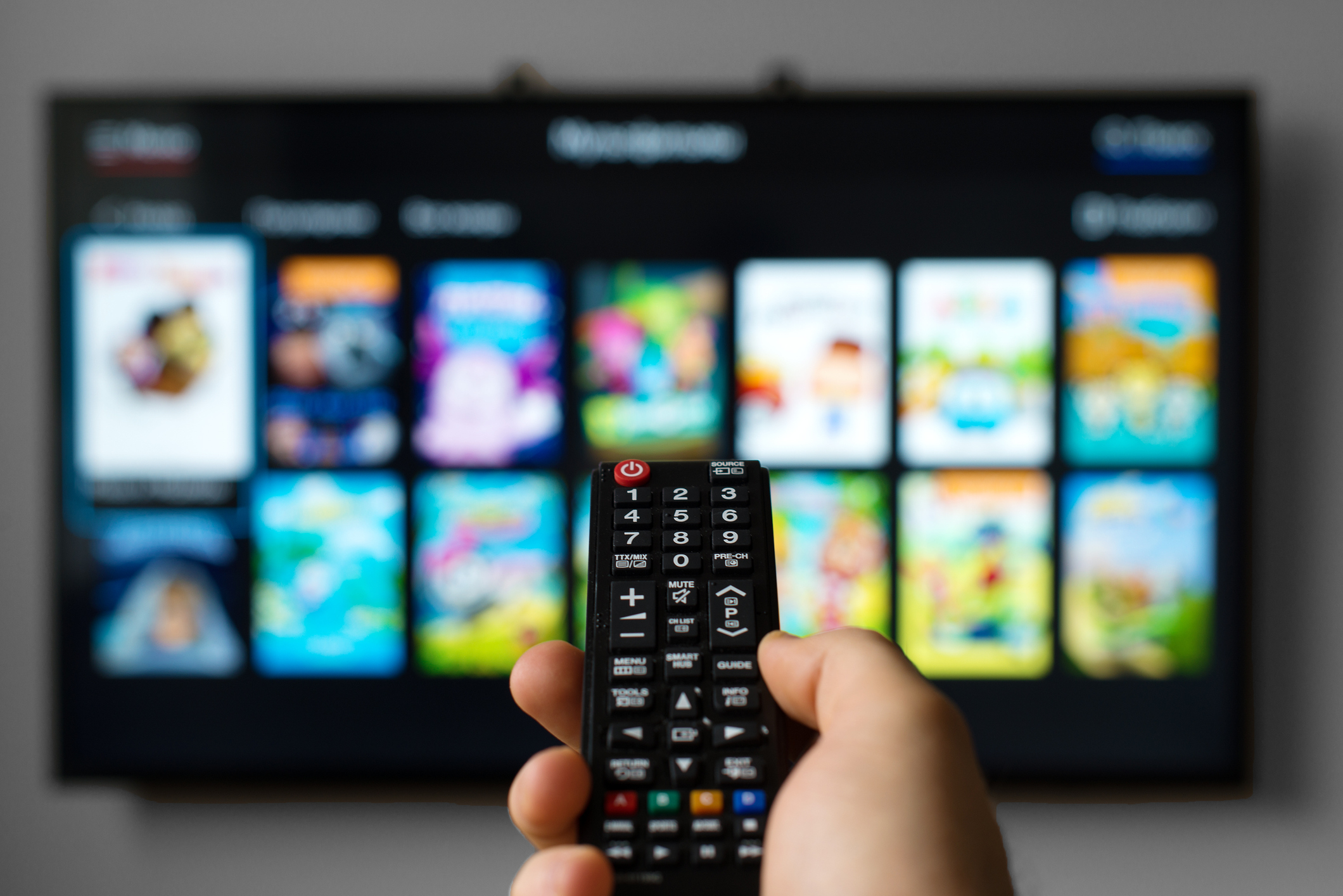 Man pointing remote toward TV and DVR