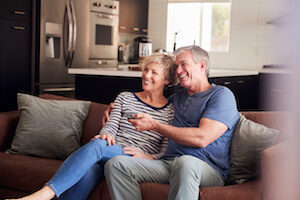 a middle-aged couple watching tv - the best tv, internet, and phone bundles - reviews.org