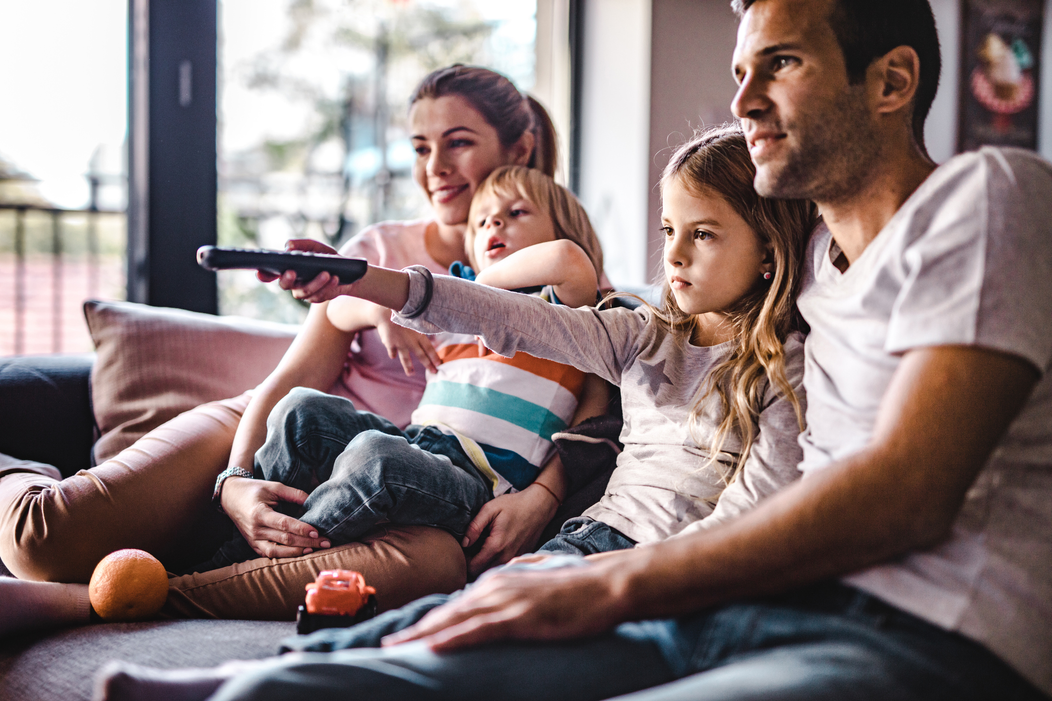 Young parents enjoying with their small kids on sofa while watching TV together.
