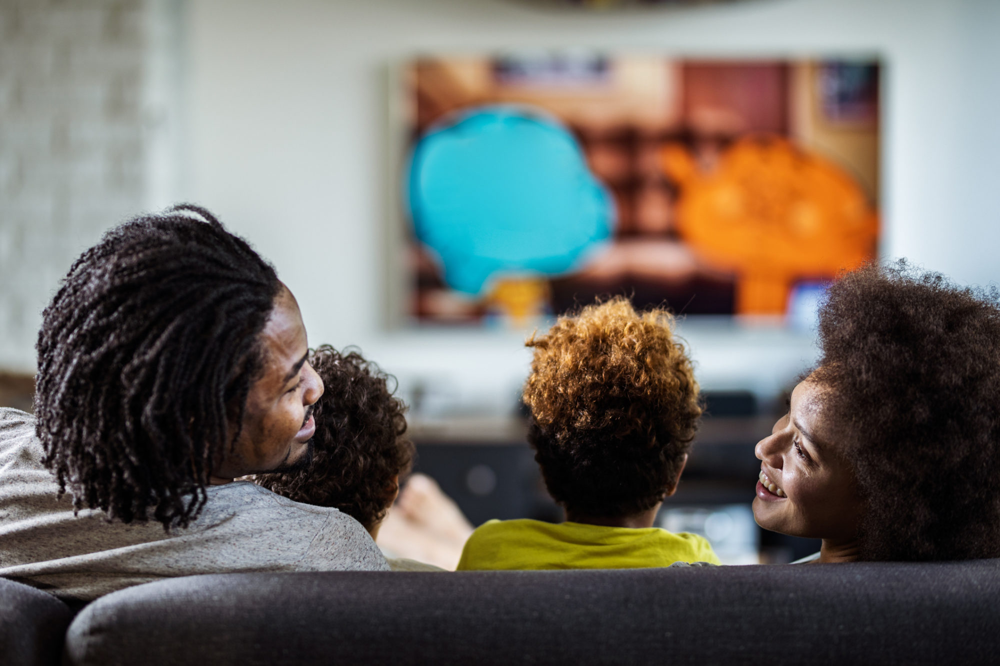Family streaming live TV in living room on couch
