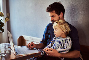 A man sits with a young boy on his lap while using a laptop