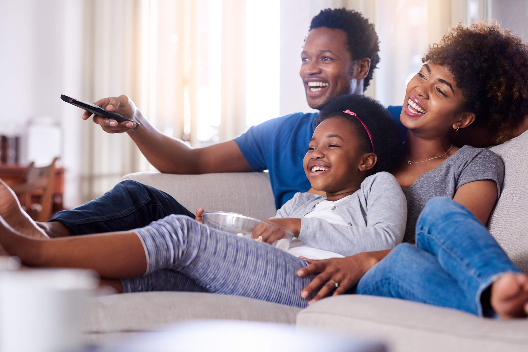 Dad, mom, and daughter cuddling on couch together watching TV in living room