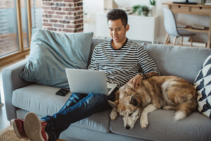 A young Asian man sits on a couch with his dog and a laptop in his lap