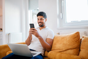 A young mixed-race man sits on a couch with his laptop and cell phone