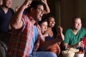 A group of friends cheering while watching a basketball game at home with snacks