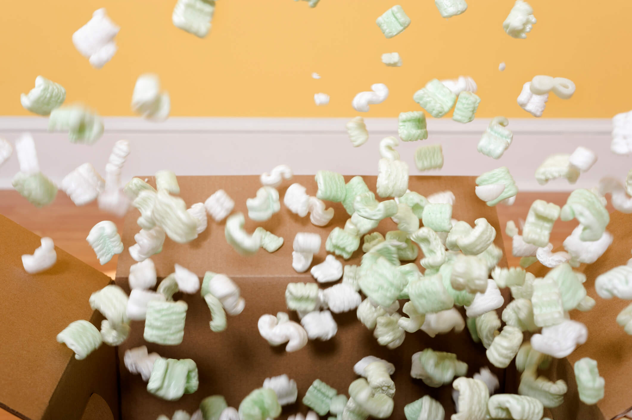 Packing peanuts burst out of a cardboard box.