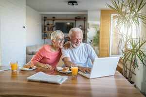 An elderly couple sits at the dining table and uses a laptop