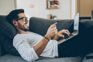 A man with dark hair and a beard pays bills on his laptop while lying on a couch