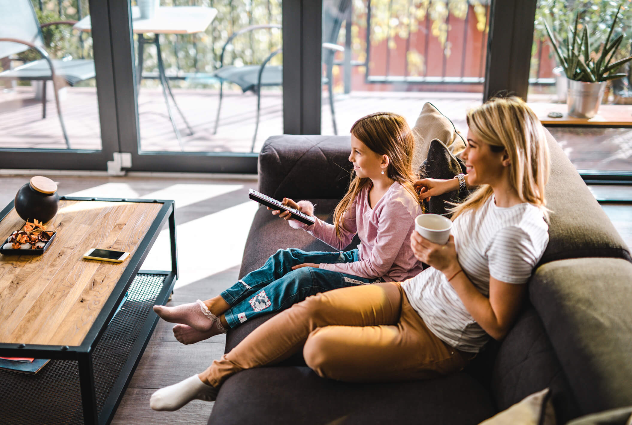 Mother and daughter watching TV on living room couch