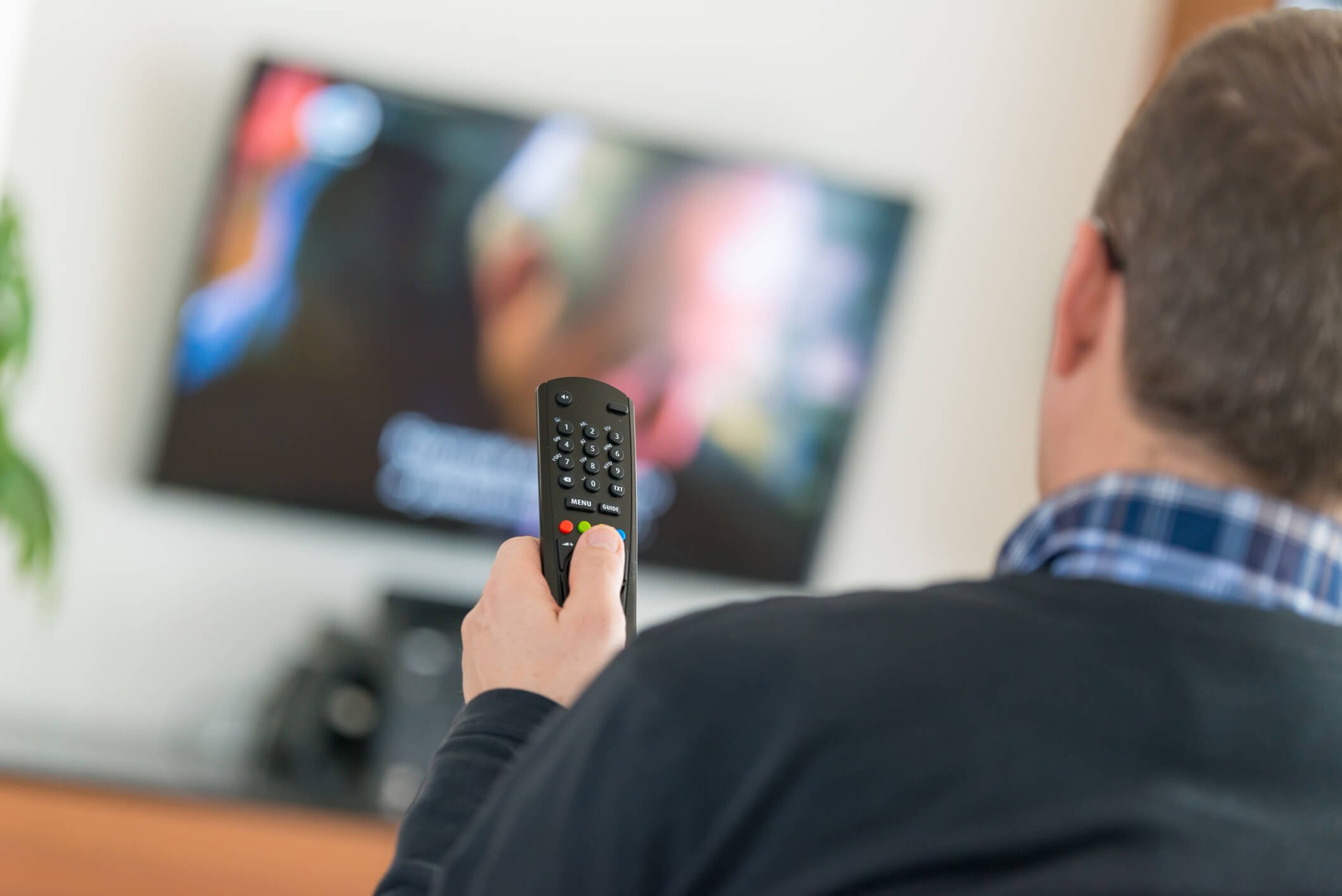 Man controlling TV with remote