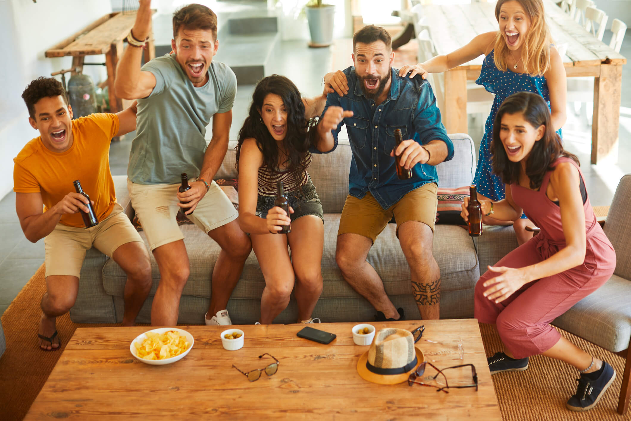 Friends getting excited while watching sports on TV in living room