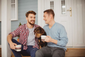 Young couple sitting with their dog on front porch of house, holding mugs