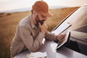 A white, bearded man uses a tablet in a rural field