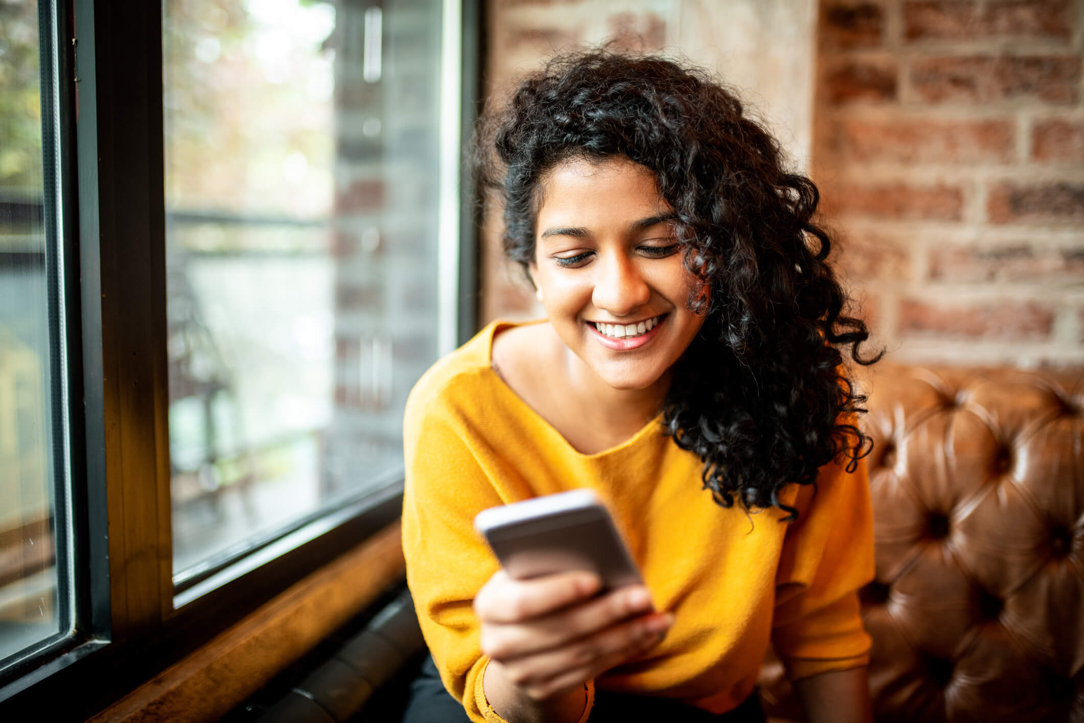 A woman with curly, dark hair and a yellow shirt looks at her phone and smiles