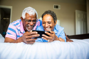 Couple laying on bed watching HBO Max on smartphone