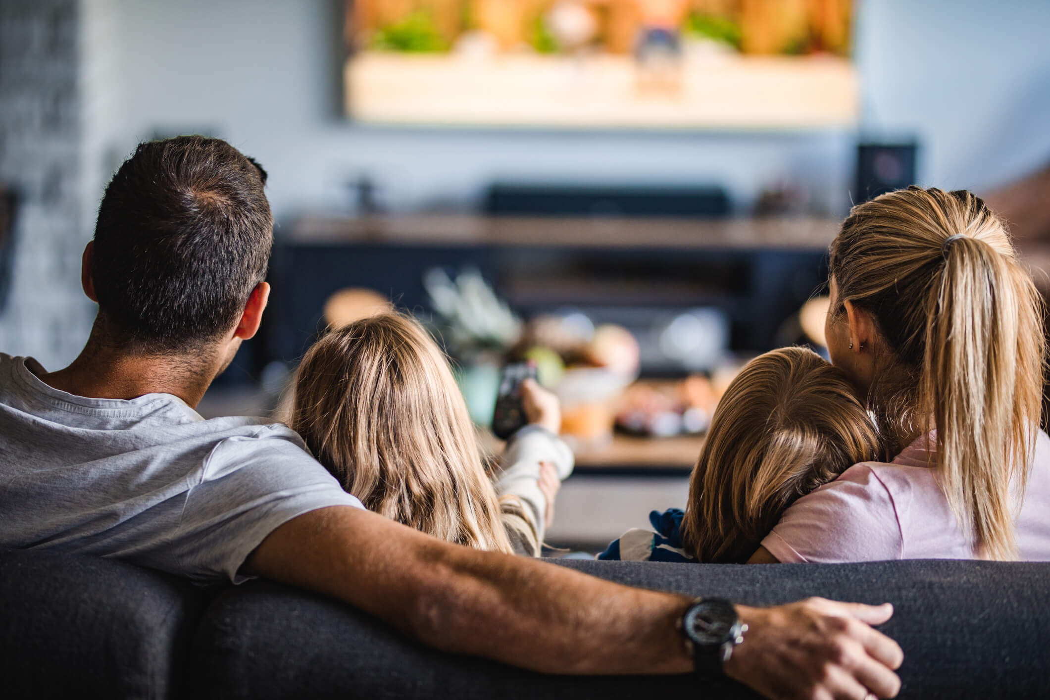 Dad, mom, daughter, and son sitting on couch watching Hulu TV