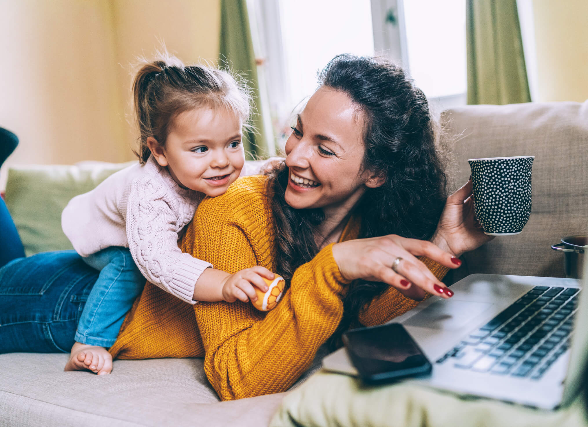 Mom and daughter laying on couch in front of laptop