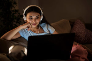 Woman watching NBC Peacock on laptop sitting on couch in the dark with headphones on