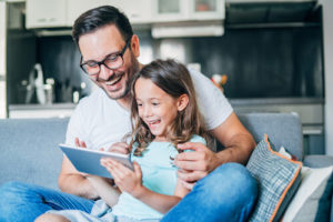 A father and daughter play games on a tablet together
